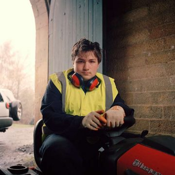 Young man sitting on lawnmower